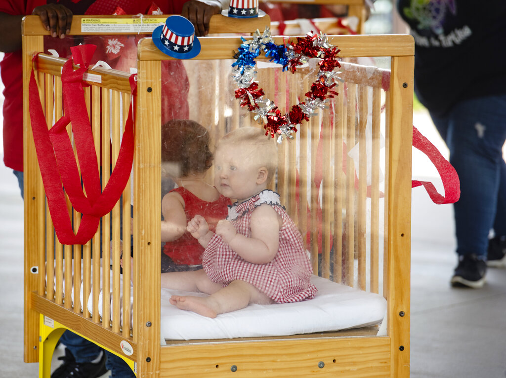 A baby from Stepping Stone School in Tyler, Texas, rides in a crib for their annual parking lot Fourth of July parade on Friday, July 3, 2020. Guests attending the event, including parents, wore face masks and viewed the parade from a distance due to the coronavirus pandemic. Stepping Stone caters to early education and preschool.