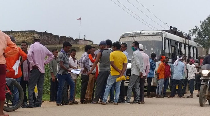 Workers wait at Vishnugarh in Hazaribagh to board a bus that will take them to Mumbai on Friday evening