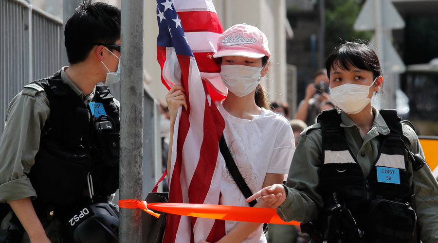 A protester is stopped by riot police during a protest outside the US consulate in Hong Kong on July 4