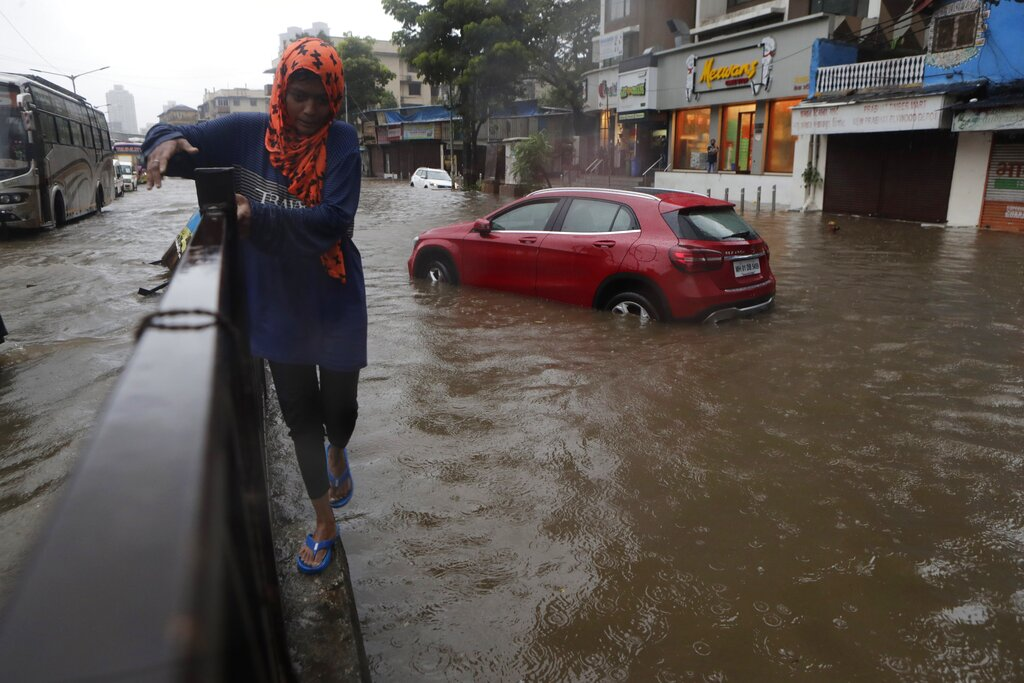 A woman walks past a waterlogged street after heavy rainfall in Mumbai, Saturday, July 4, 2020.