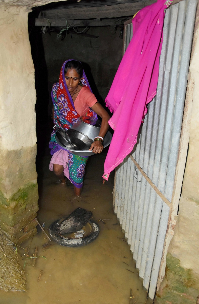 A woman shifts her utensils as flood-water enters her house in Bind Toli area along the banks of River Ganga, following heavy monsoon rain, in Patna, Saturday, July 4, 2020