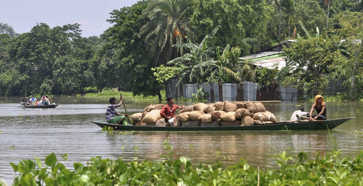 Villagers cross a flooded area on a boat, at Jhargaon in Morigaon district, Tuesday, June 30, 2020