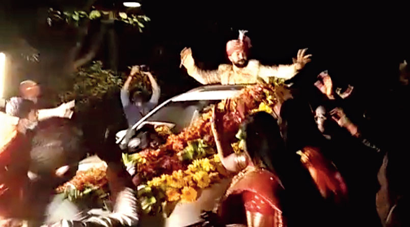 Groom in the open car during the marriage procession.