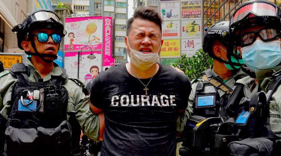 Police detain a protester after spraying pepper spray during a protest in Causeway Bay in Hong Kong, Wednesday, July. 1, 2020.