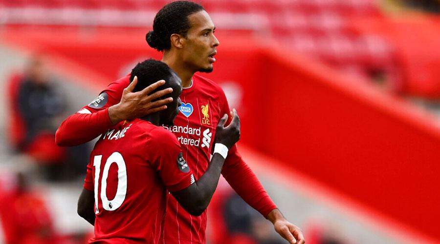 Liverpool's Sadio Mane, left, celebrates with Virgil van Dijkafter scoring the opening goal against  Aston Villa on Sunday