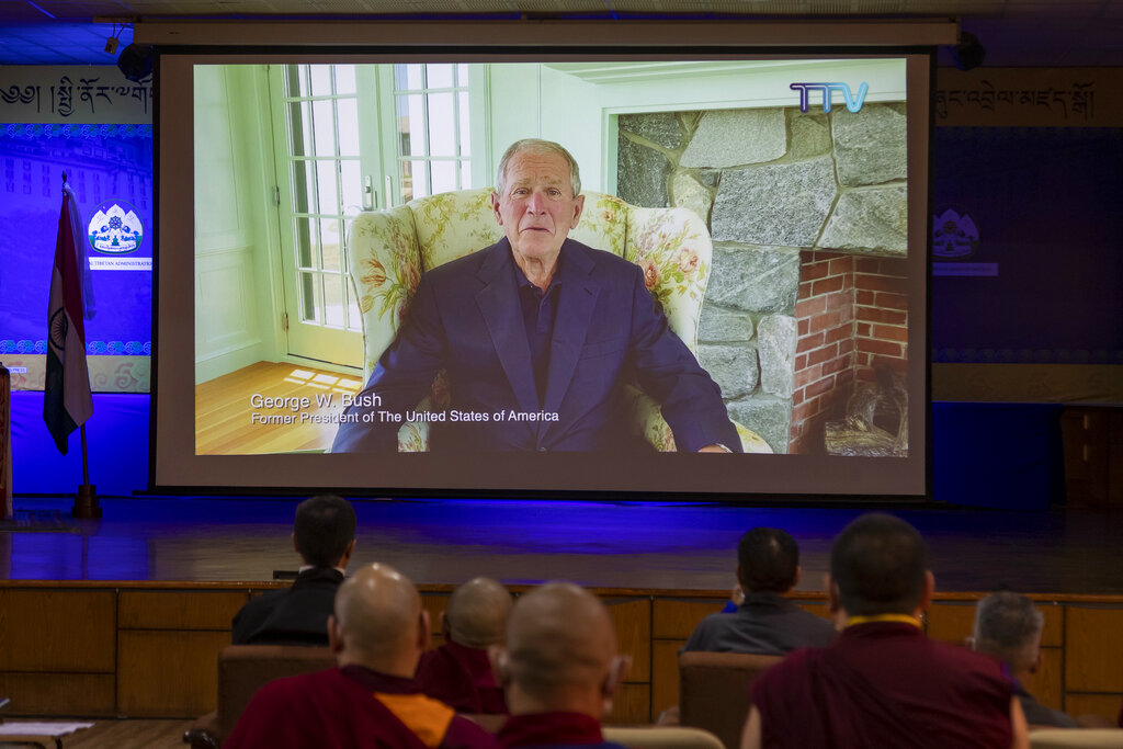 Exile Tibetans watch as former U.S. president George W. Bush delivers a video message to greet Tibetan spiritual leader the Dalai Lama on his the 85th birthday at an official function in Dharmsala, India, Monday, July 6, 2020.