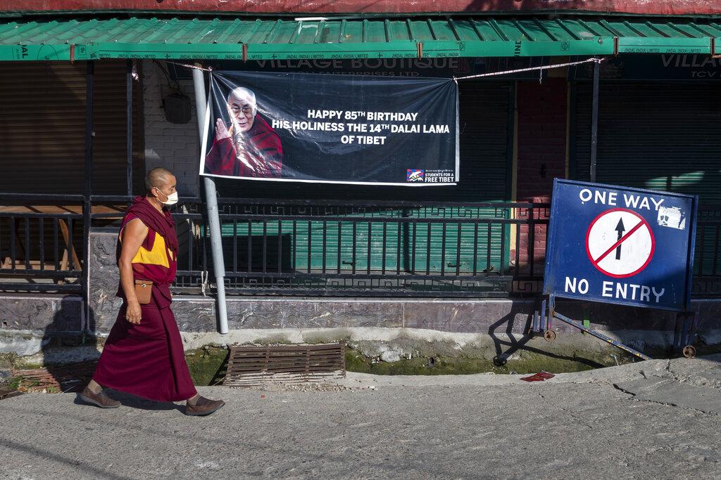 An exile Tibetan Buddhist monk walks past a banner wishing Tibetan spiritual leader the Dalai Lama on his 85th birthday in Dharmsala, India, Monday, July 6, 2020.
