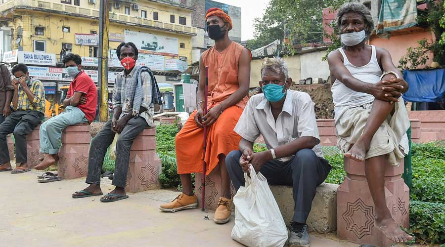 Homeless people wait for food outside Gauri Shankar Temple during Unlock 2.0, in New Delhi, Monday, July 6, 2020.