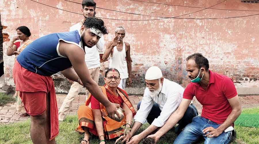 Social activist Akhlaque Ahmad (right in red T-shirt) and others plant a sapling at Tiwari Mandir in Dhanbad's  Jhariaon Monday