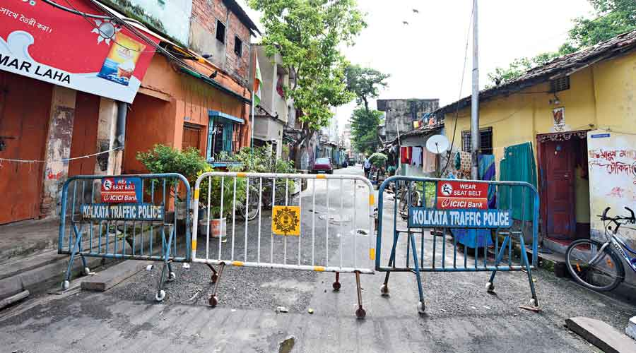 Barricades at the entrance to Maratha Ditch Lane in north Calcutta on Tuesday afternoon. Police have placed the guardrails to prevent residents from moving in and out of the area to slow down the spread of Covid-19.