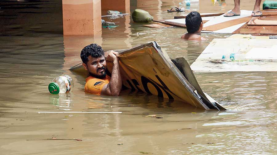 A resident carries billboards in the flooded locality of Hatigaon after heavy rains in Guwahati on Tuesday.