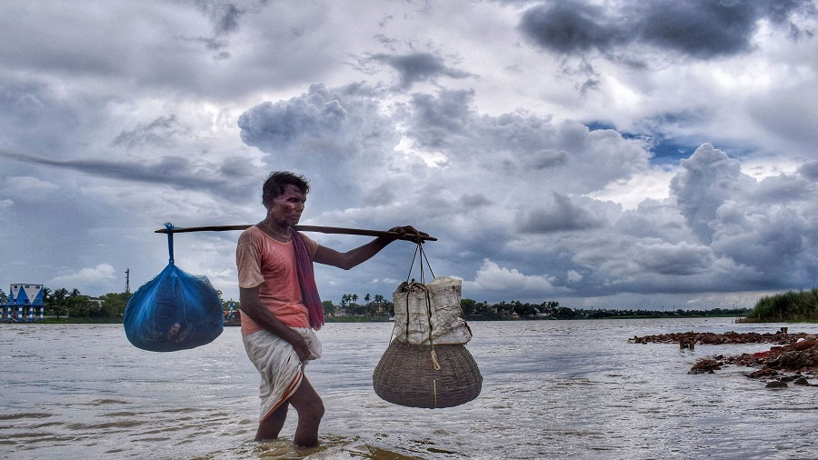 A man carrying his belongings walks at the banks of Hooghly river in the backdrop of dark clouds looming in the sky, in Nadia district