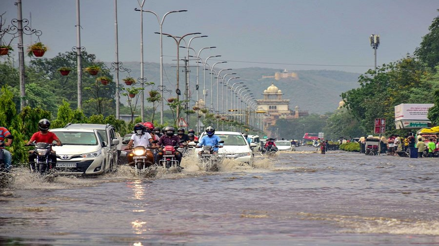 Commuters pass through a waterlogged street following heavy rain, in Jaipur, Tuesday, July 7, 2020.