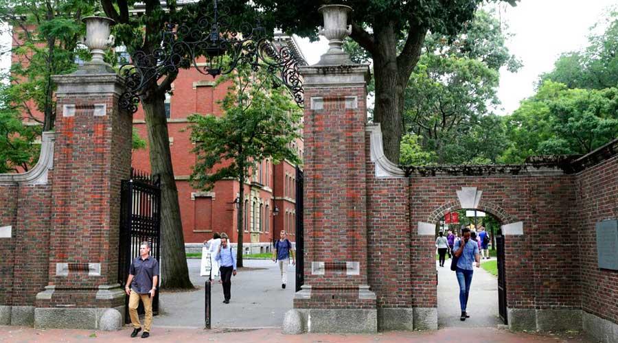 In this Aug. 13, 2019, file photo, pedestrians walk through the gates of Harvard Yard at Harvard University in Cambridge, Massachusetts