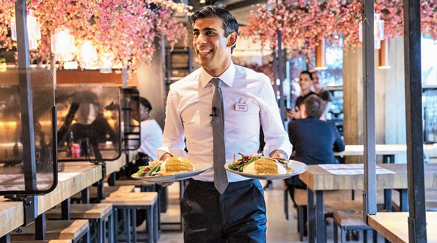 Chancellor Rishi Sunak serves food at a Wagamama outlet in London on July 9.
