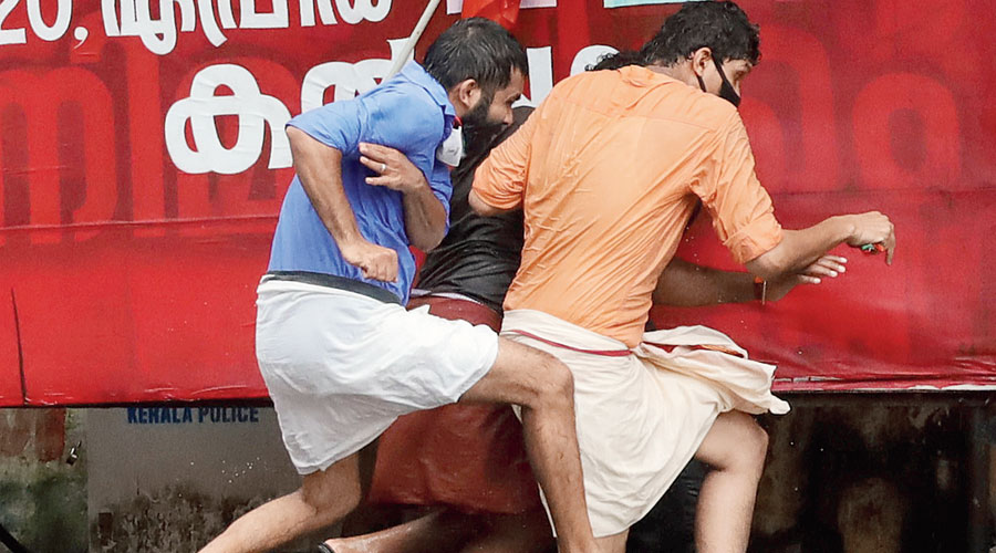 BJP youth wing members try to escape police action during a protest in Kozhikode, Kerala, over the gold smuggling case on Friday.