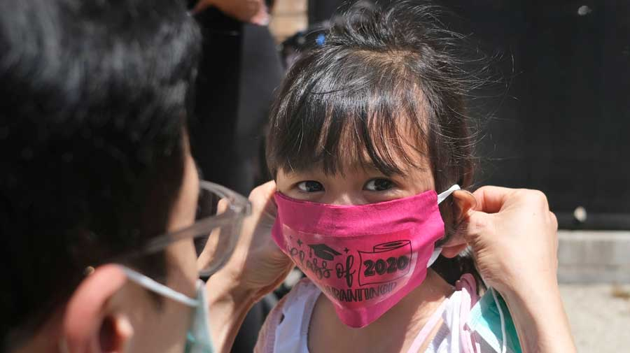In this June 10, 2020, file photo, a girl's father helps her with a new mask she received during a graduation ceremony in New Jersey.