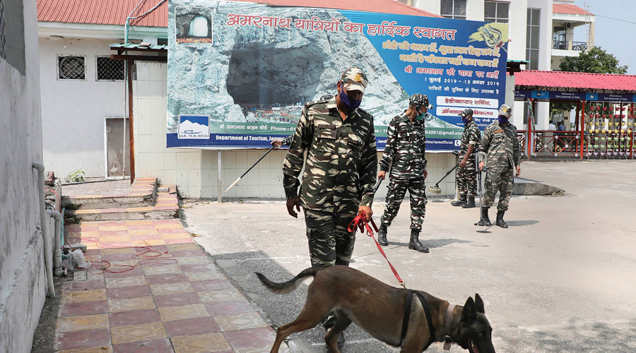 CRPF officers with a sniffer dog inspect the Yatri Niwas Bhagwati Nagar premises for the upcoming Amarnath Yatra in Jammu on Saturday.