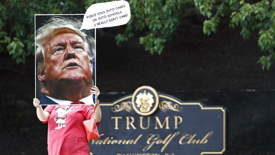 A protester holds a sign as US President Donald Trump visits Trump National Golf Club in Sterling, Virginia.