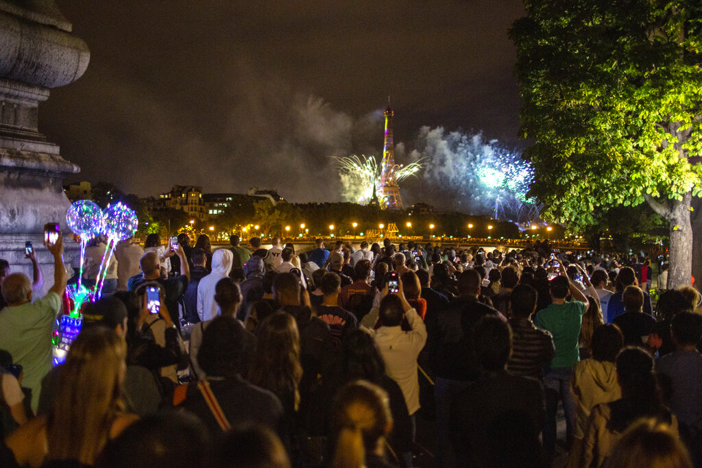 People attend the fireworks display by the Eiffel Tower in Paris during Bastille Day celebrations late Tuesday, July 14, 2020. Bastille Day marks the July 14, 1789, storming of the Bastille prison by angry Paris crowds that helped spark the French Revolution.