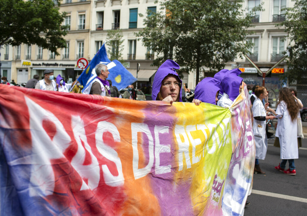 Hospital workers demonstrate on Bastille Day in Paris, Tuesday, July 14, 2020. French hospital workers are protesting to demand better pay and more investment in France's public hospital system, which is considered among the world's best but struggled to handle a flux of virus patients after years of cost cuts.