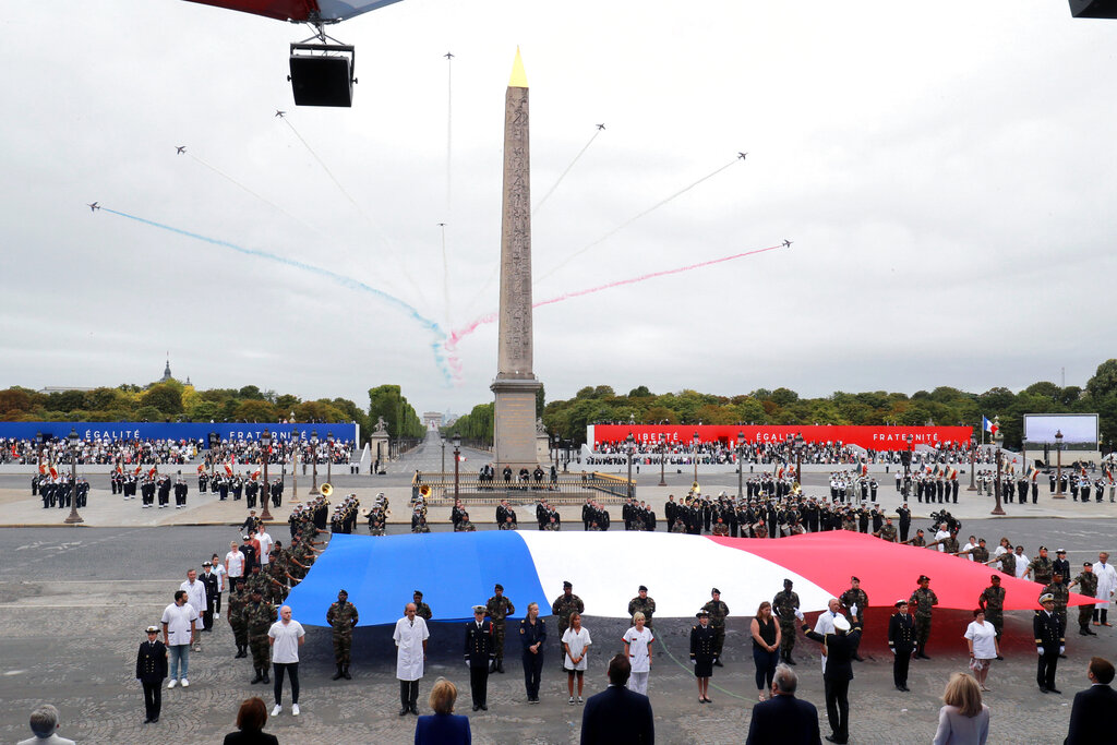 Members of medical staff pose with the French flag as they take part in the annual Bastille Day military ceremony on the Place de la Concorde in Paris, Tuesday, July 14, 2020. France are honoring nurses, ambulance drivers, supermarket cashiers and others on its biggest national holiday