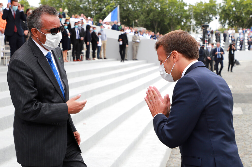 France's President Emmanuel Macron, right, greets Director General of the World Health Organization, Tedros Adhanom Ghebreyesus, at the end of the Bastille Day military parade, Tuesday, July 14, 2020 in Paris.
