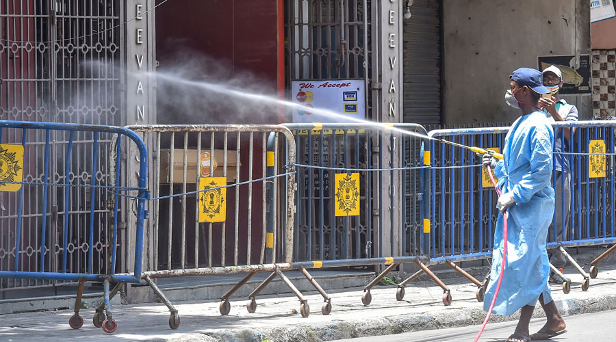A municipal worker sprays disinfectant at a sealed residential area  during Unlock 2.0 in Calcutta.