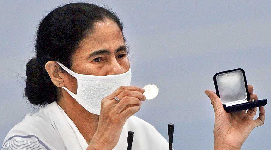 Mamata Banerjee shows a medal that has been awarded to Covid-19 frontline workers. The Bengal cabinet has approved a policy to offer jobs to the next of kin of the state government employees who die from Covid while on duty to fight the spread of the disease.