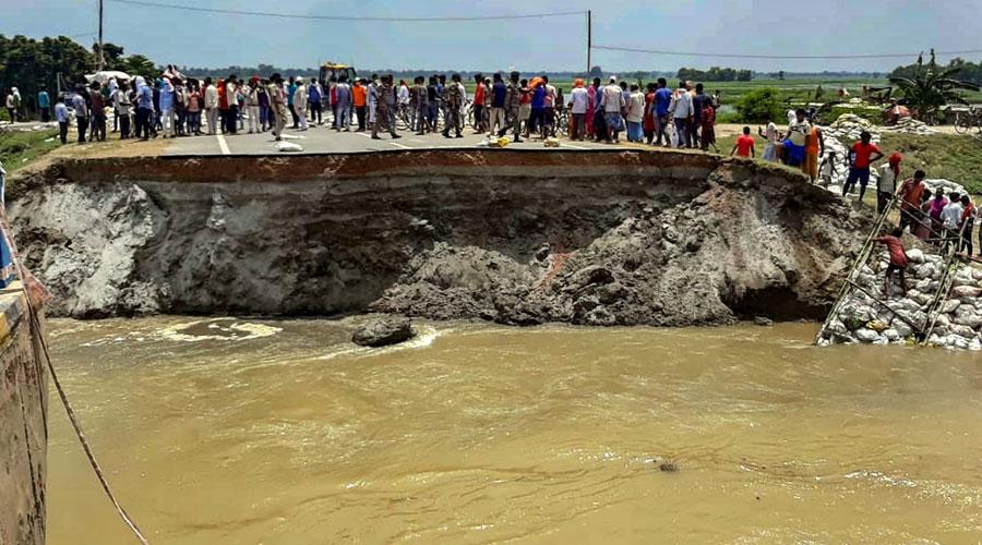 People stand near the washed away Sattarghat Bridge following heavy rainfall in Gopalganj on Thursday.