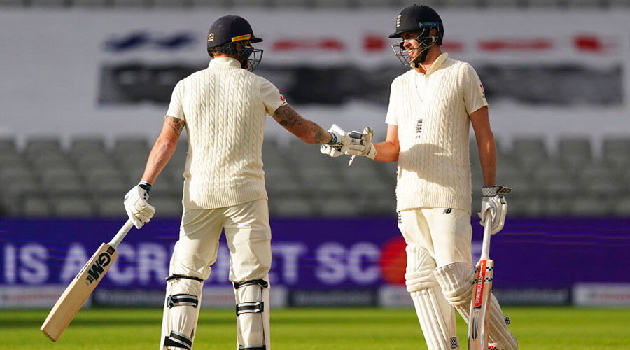 England's Ben Stokes, left, and Dom Sibley tap their gloves at the end of the first day of the 2nd Test match between England and West Indies on Thursday