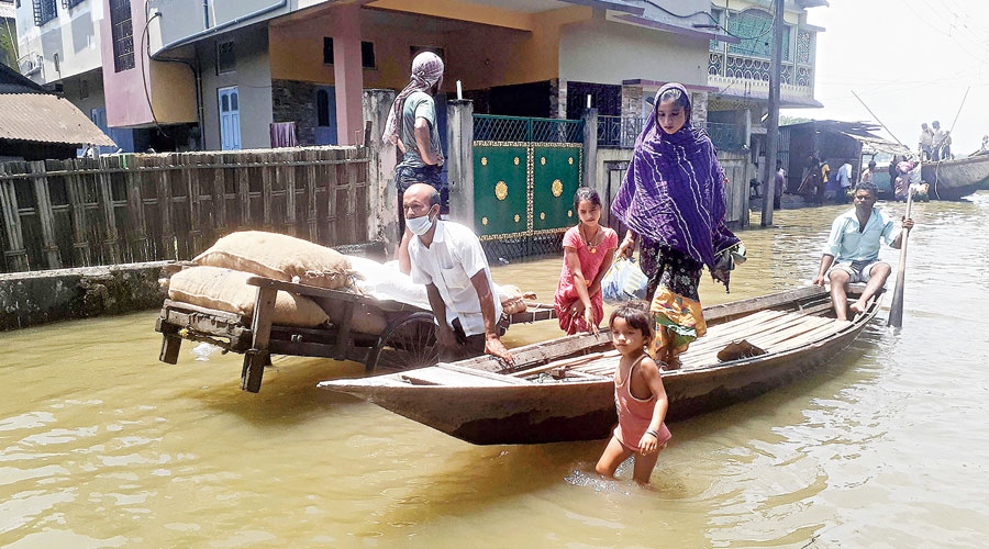 Flood-affected people move to a safer place in Assam's Dhubri district on Friday.
