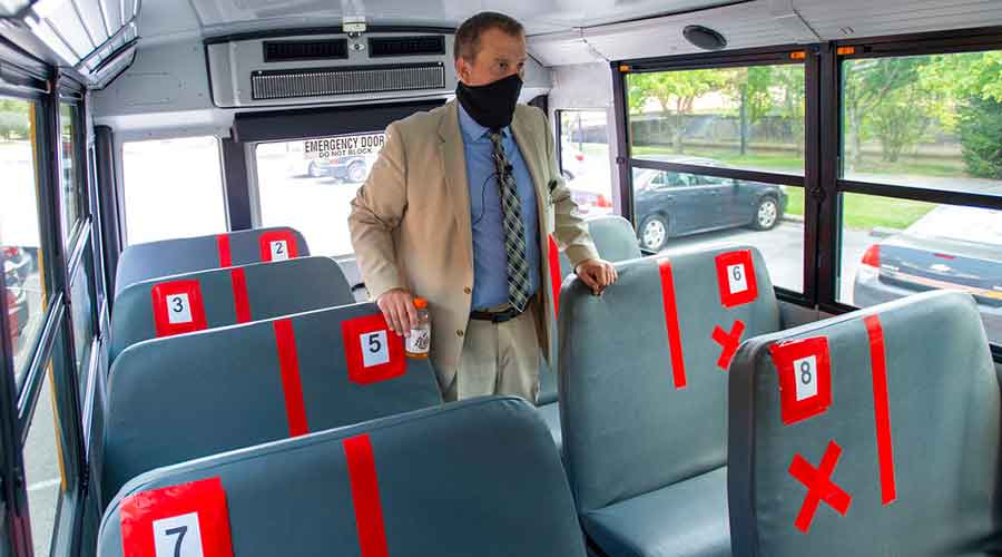 A superintendent shows the new seating configuration on the school buses for the upcoming school year, Thursday, July 16, 2020, in Bristol, Virginia.