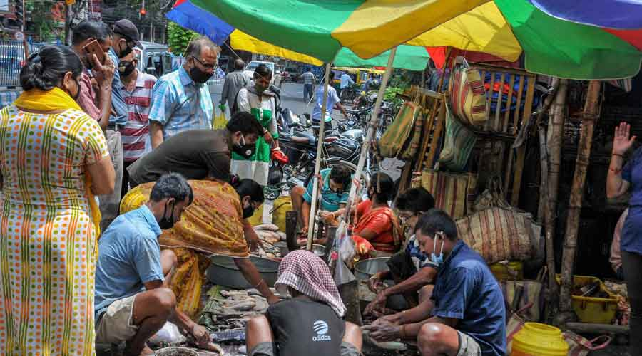People, not adhering to social distancing norms, buy fish from roadside vendors on Sunday