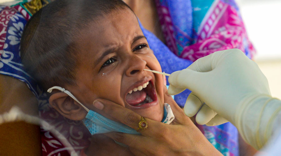 A medic collects a sample from a child for Covid-19 test in New Delhi on Saturday, July 18, 2020.