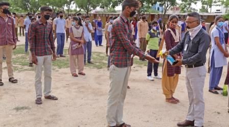 Beawar, Rajasthan, India, June 29, 2020: A teacher pumps sanitizer on the hands of students before appear in the 10th standard board exam.
