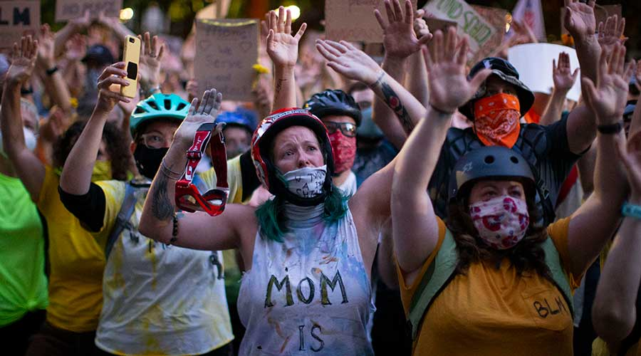 Protesters gesture during protests in Portland, Oregon on Monday