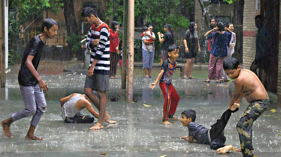 Children play in front of a temple during heavy rain in Noida on Tuesday.