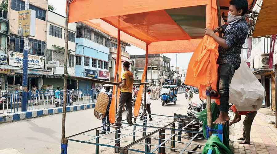 Workers dismantle the dais in front of the BJP district office in Raiganj
