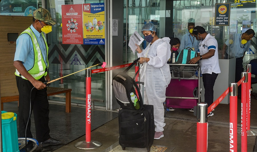 Workers sanitise passenger baggage in front of the entry gate at NSCBI Airport, during weekly two-day complete lockdown to curb the spread of coronavirus disease, in Calcutta, Thursday, July 23, 2020.