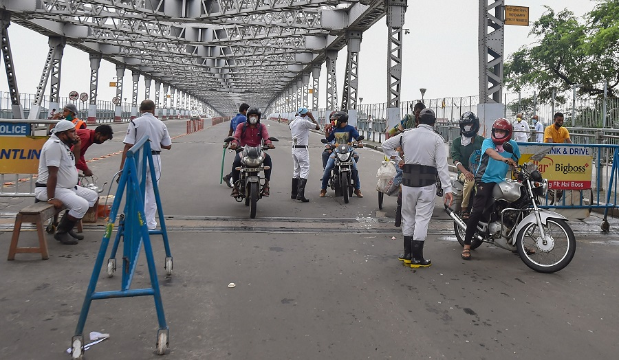 Police personnel stop commuters at Howrah Bridge, during the complete lockdown in the state to curb the spread of coronavirus, in Calcutta, Thursday, July 23, 2020.