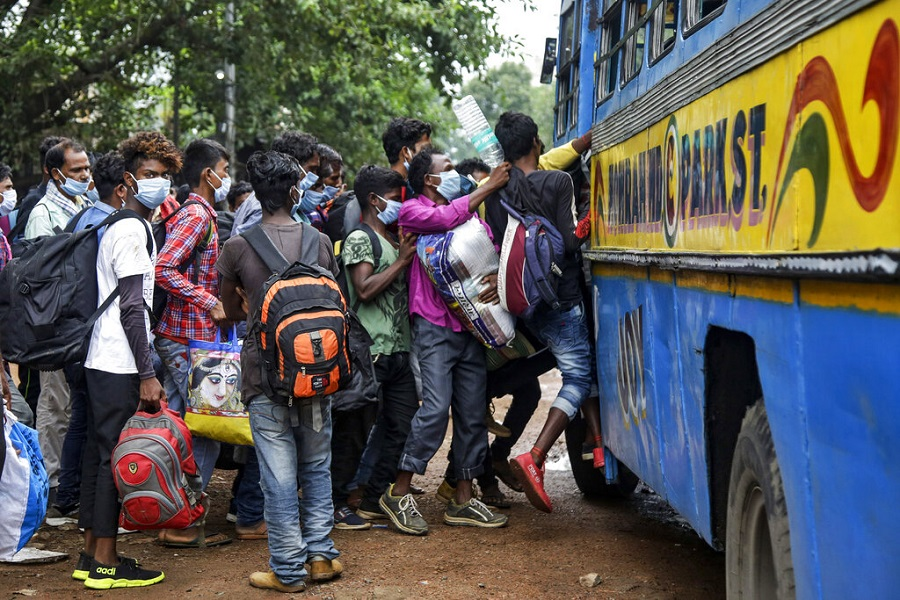 Commuters wearing face masks jostle for a ride on a bus discarding social distancing guidelines in Calcutta, Tuesday, July 21, 2020.
