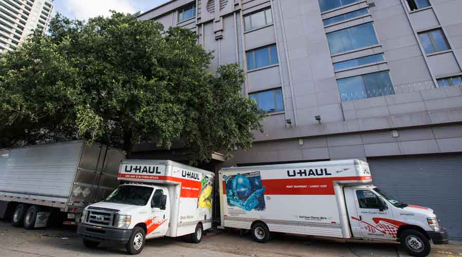 Moving trucks are parked outside the Consulate General of China on Friday, in Houston