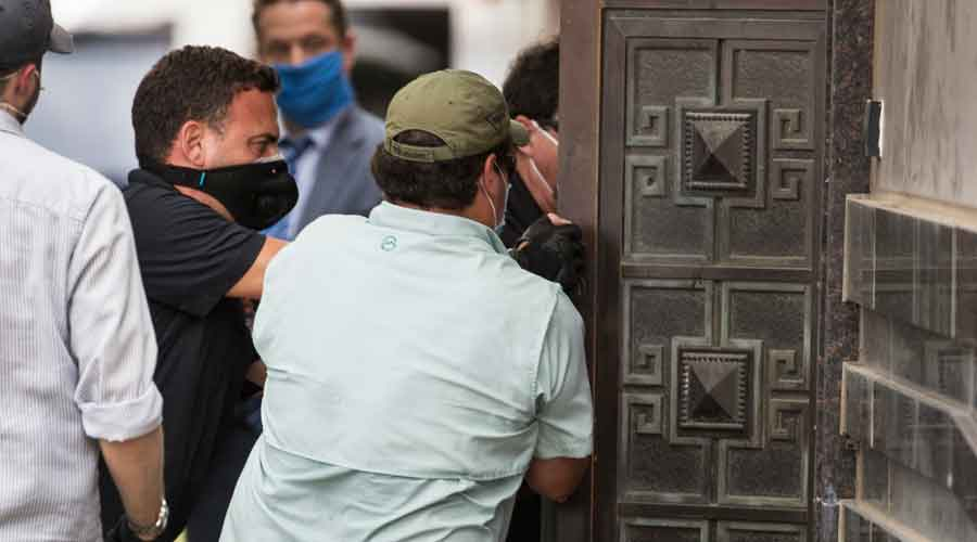 Federal officials and a locksmith pull on a door to make entry into the vacated Consulate General of China building on Friday