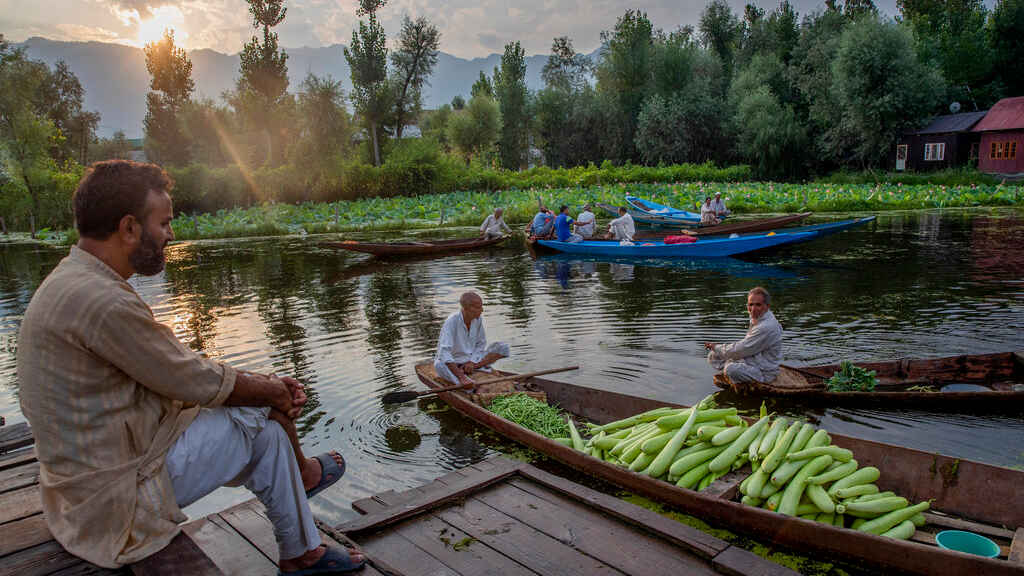 A Kashmiri man watches others sell their produce at the floating vegetable market on the Dal Lake in Srinagar, Sunday, July 26, 2020.