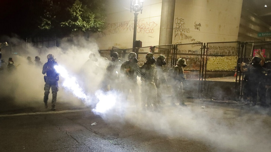 Federal officers deploy tear gas as they try to disperse a crowd during a Black Lives Matter protest at the Mark O. Hatfield United States Courthouse in Portland on Monday