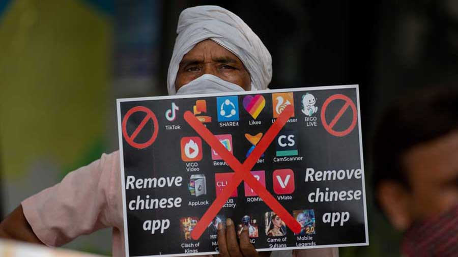 A man holds a placard with logos of Chinese apps during a protest against China in New Delhi on Tuesday.