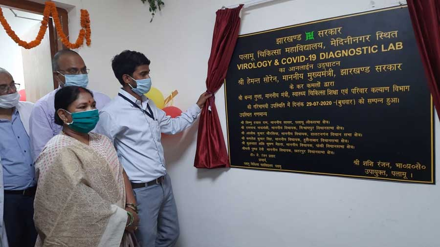 DC Palamau Shashi Ranjan (curtain in hand) manually unveiling the inauguration plaque of the virology and Covid-19 diagnostic lab in Palamau Medical College