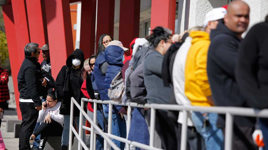 In this March 17, 2020, file photo, people wait in line for help with unemployment benefits at the One-Stop Career Center in Las Vegas.