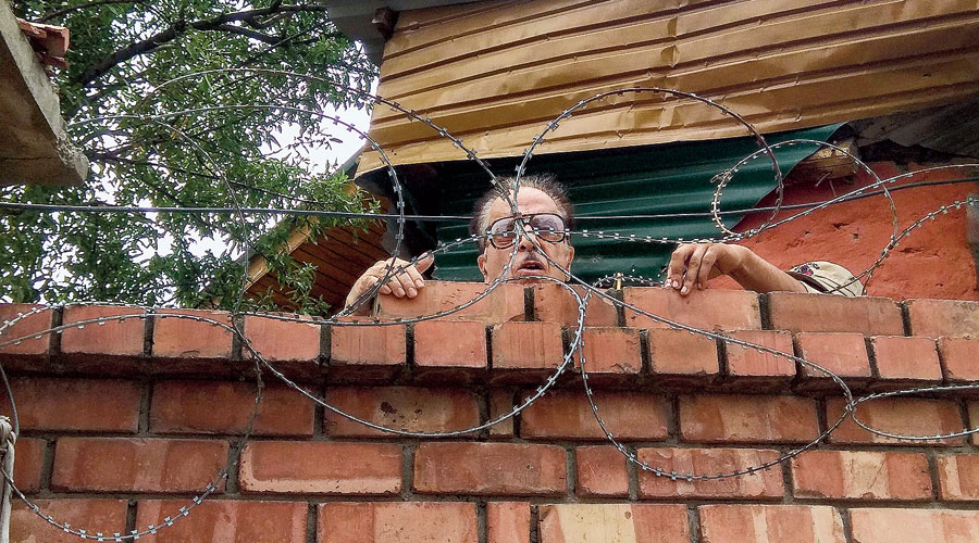 Former Union minister Saifuddin Soz, 82, speaks to journalists from behind the barbed wire at his home in Srinagar on Thursday.